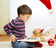 Cute boy reading a fairy tale. New Year Royalty Free Stock Image