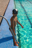 Cute boy ready to dive in the sport swimming poolb standing on border near pool ladder.  Royalty Free Stock Photos