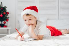 Boy in a red cap writes a letter to Santa Royalty Free Stock Photos