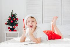 Boy in a red cap writes a letter to Santa Royalty Free Stock Image