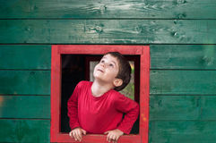 Cute boy on red framed window Royalty Free Stock Photo