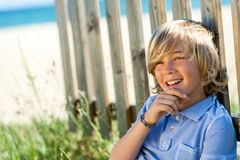 Cute boy relaxing next to wooden fence. Stock Photo