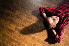 Cute boy relaxing on wooden floor. Overhead view of cute boy relaxing on wooden floor Royalty Free Stock Photo