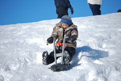 Cute boy riding motorcyle sled downhill looking scared. Royalty Free Stock Images