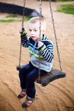Cute boy riding on a swing royalty free stock image