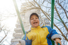 A cute boy is riding a swing in the playground. Cute child, boy, having fun on a swing in the on sun Royalty Free Stock Images