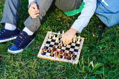 Cute boy in riound glasses and blue shirt sits on the grass in the park and plays chess at wooden chessboard. Hobby, education stock photography