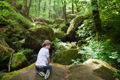 Cute boy on the rocks near a scenic waterfall Royalty Free Stock Images