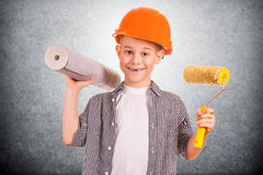 Cute boy with a roll of wallpaper and brush Royalty Free Stock Photo