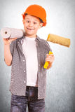 Cute boy with a roll of wallpaper and brush Stock Image