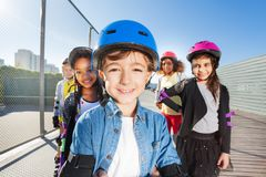 Cute boy rollerblading with friends outdoors Stock Image