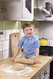 Cute boy rolling dough. Beautiful boy sitting on the kitchen counter holding a rolling pin. making bread or pizza Stock Photo