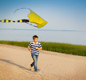 Cute boy running with fly kite beach outdoor Royalty Free Stock Images