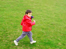 Cute boy running on green meadow Stock Photos