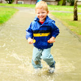 Cute boy running through puddle after the rain Stock Image