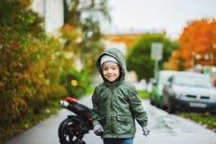 A cute boy runs along the road and smiles stock photos