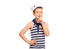 Cute boy in a sailor outfit holding a finger on lips Royalty Free Stock Image