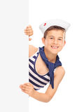 Cute boy in a sailor outfit posing behind a panel Stock Photo