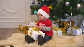 Cute boy in a santa hat and bow tie tying a ribbon on a gift stock video footage