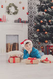 Cute boy in santa hat and christmas presents Stock Image