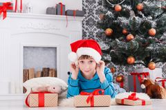 Cute boy in santa hat unwrapping christmas presents Royalty Free Stock Photo