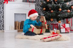 Cute boy in santa hat unwrapping christmas presents Royalty Free Stock Photography