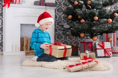 Cute boy in santa hat unwrapping christmas presents. Cute happy boy in santa hat unwrap christmas present box on holiday morning in beautiful room interior. Male Stock Photo