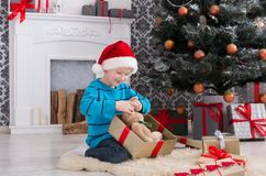 Cute boy in santa hat unwrapping christmas presents. Cute happy boy in santa hat unwrap christmas present box on holiday morning in beautiful room interior. Male Stock Photography