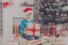 Cute boy in santa hat unwrapping christmas presents Stock Photos