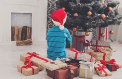 Cute boy in santa hat unwrapping christmas presents. Cute happy boy in santa hat unwrap christmas present box on holiday morning in beautiful room interior. Male Royalty Free Stock Image