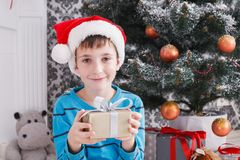 Cute boy in santa hat unwrapping christmas presents Stock Photo
