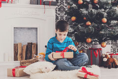 Cute boy in santa hat unwrapping christmas presents Stock Image
