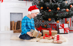 Cute boy in santa hat unwrapping christmas presents Royalty Free Stock Image