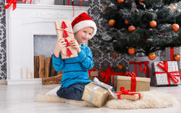 Cute boy in santa hat unwrapping christmas presents Stock Images