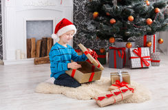 Cute boy in santa hat unwrapping christmas presents Royalty Free Stock Images