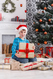 Cute boy in santa hat unwrapping christmas presents Royalty Free Stock Photos