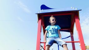 Cute boy of seven years having fun on a playground outdoors in summer. Slow motion . Joyful active childhood. stock video