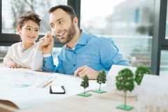 Cute boy sharing earpieces with his father. Generous child. Cheerful little boy sitting at the table next to his father and sharing earpieces with him while Stock Image