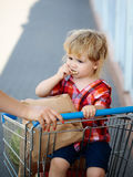 Cute boy in shopping trolley Stock Photography