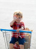 Cute boy in shopping trolley Royalty Free Stock Photo