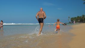 Cute boy in shorts with daddy runs along picturesque beach