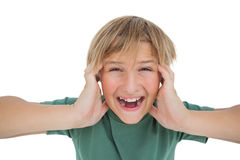 Cute boy shouting and covering his ears Stock Photos