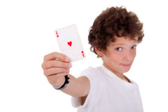 Cute boy showing an ace of hearts. Isolated on white, studio shot Stock Photos
