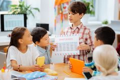 Cute boy showing a table to the mates. Confidence. Cute smart boy showing a table to the mates while standing in a class royalty free stock photos
