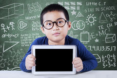Cute boy shows tablet screen in the class Royalty Free Stock Photos