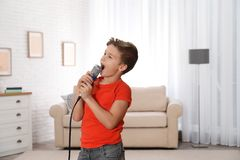 Cute boy singing in microphone royalty free stock photo