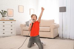 Cute boy singing in microphone stock photo