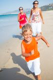 Cute boy with sister and mother on the beach Stock Photos