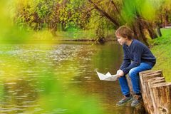 Cute boy sits near pond holding white paper boat Stock Image