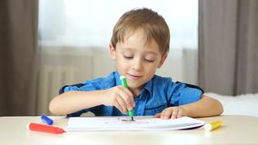 A cute boy sits at a table in a room and spends time painting with colored felt pen. stock footage